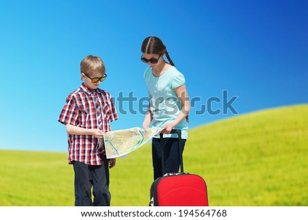 Children going for vacation with a luggage and a map - stock photo