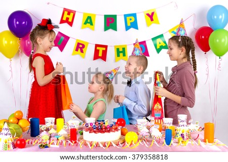 Children greet a girl in a red dress, on the table sweets, balloons