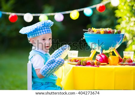 Children grilling meat. Family camping and enjoying BBQ. Little boy at barbecue preparing steaks, kebab and corn. Kids eating grill and healthy vegetable meal outdoors. Garden party for toddler child - stock photo