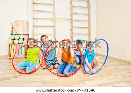 Children group playing with hula hoops - stock photo
