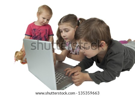Children group two girls and one boy playing on a silver laptop isolated on white background