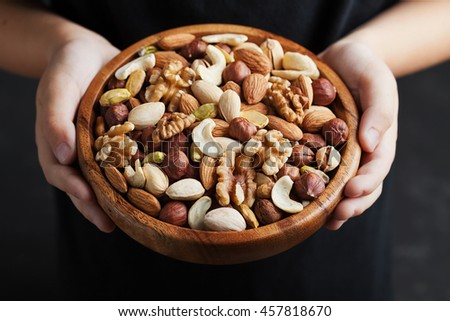 Children hands holding a wooden bowl with mixed nuts. Healthy food and snack. Walnut, pistachios, almonds, hazelnuts and cashews. - stock photo