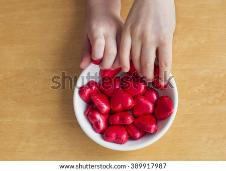 Children hands reaching for chocolate sweets in shape of hearth in a bowl on a table, top view.