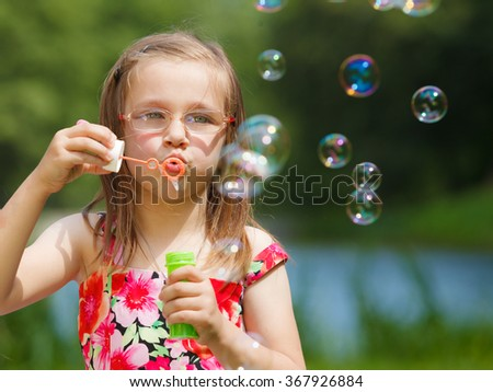 Children happiness and carefree concept. Little girl having fun blowing soap bubbles in park green blurred background