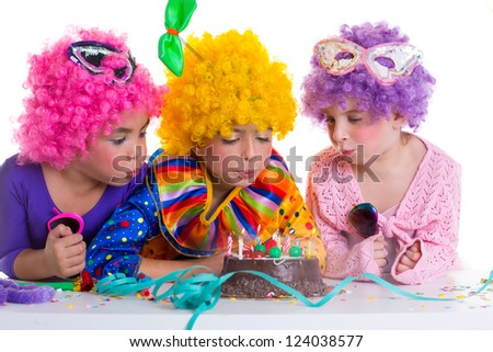 Children happy birthday party with clown wigs blowing chocolate cake candles