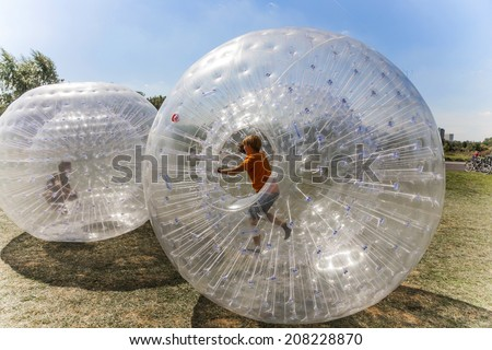 children have a lot of fun in the Zorbing Ball - stock photo