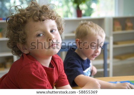 Children have fun and learn while playing a board-game at the preschool class. - stock photo