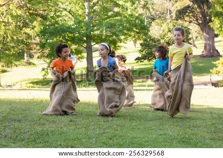 Children having a sack race in park on a sunny day - stock photo
