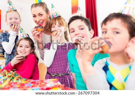 Children having cupcakes celebrating birthday on big party with all the friends and mom - stock photo