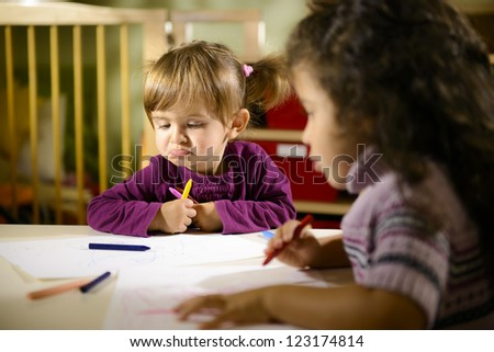 Children having fun at school, two young girls drawing in kindergarten with sad child contemplating her drawing