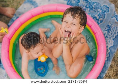 Children having fun in inflatable pool - stock photo