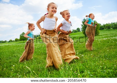 Children having fun jumping in sacks on a meadow - stock photo