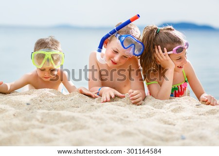 Children having fun on the beach. Scuba diving - stock photo