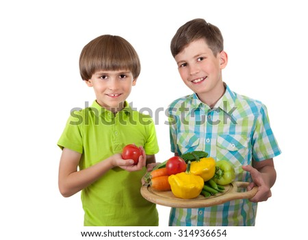 Children hold cutting board with fresh vegetables isolated on white background - stock photo