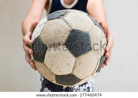 Children hold the old football - stock photo