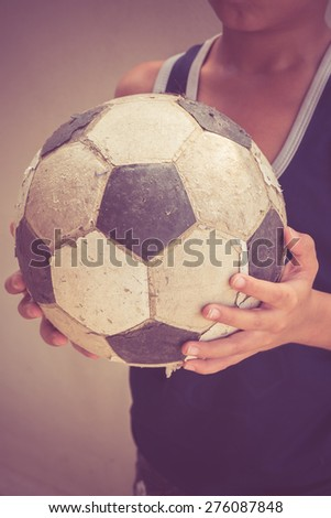 Children hold the old football with filter effect retro vintage style - stock photo
