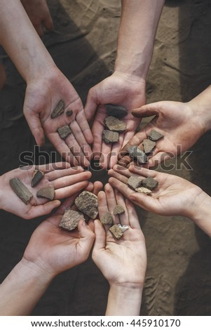 Children holding archaeological finds stones