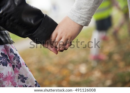 Children holding hands, one black and one white.