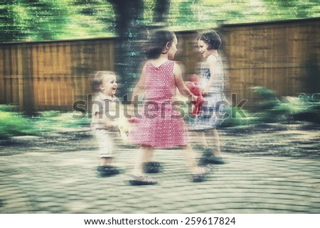 Children holding hands playing circle games with colorful plush bunny rabbits outside in a garden during an Easter party.  Intentional motion blur effect.  Filtered for a retro, vintage look. - stock photo