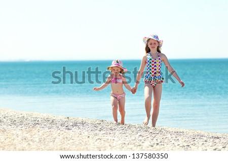 Children holding hands running on beach - stock photo