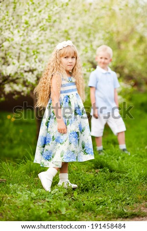 Children in a blossoming garden of apple-trees - stock photo