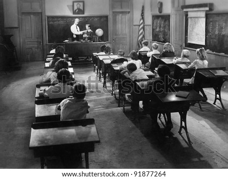 Children in a class room with a teacher - stock photo