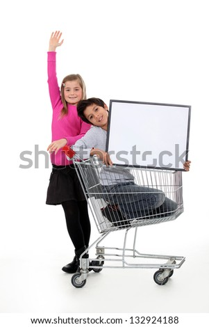 Children in a shopping trolley with a blank board - stock photo