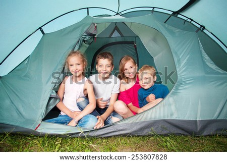 Children in a tent. Camping. Happy kids at summer vacations - stock photo