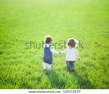 Children in beautiful spring green field - stock photo