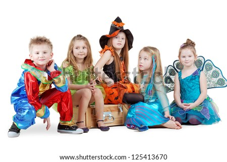 Children in carnival costumes sit on chest and on floor near it - stock photo