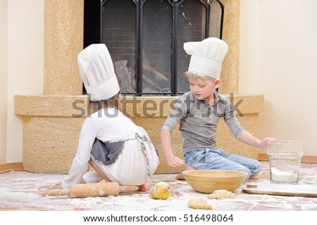 Children in chef's hats near the fireplace: a girl dressed in a toque sitting back to camera and playing cook with her blue eyed cousin, they are totally stained with flour