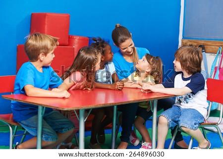 Children in circletime listining to girl talking in kindergarten - stock photo
