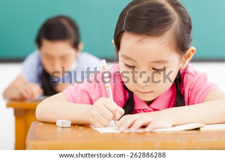 children in classroom with pen in hand - stock photo