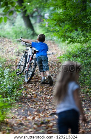 Children in forest mountain. A little boy walking with his bike high up - stock photo