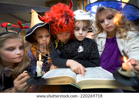 children in halloween costumes read witchcraft book - stock photo