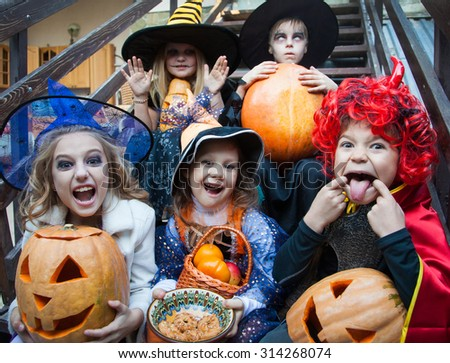 Children in halloween costumes show funny faces - stock photo