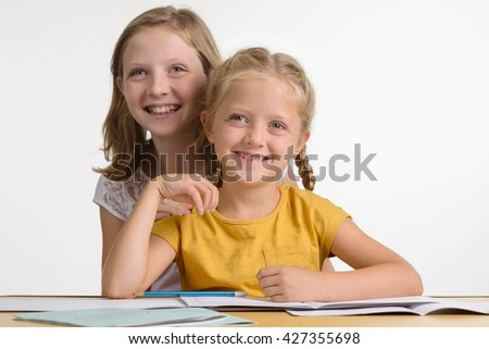 Children in interest group have a lot of fun while doing their favorite things. Two sisters with marvelous smiles look not in the camera. Close-up portrait of beautiful young ladies. - stock photo