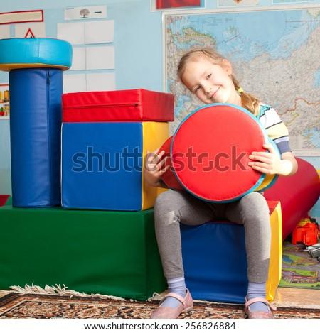 Children in kindergarten. Kids in nursery school. Girl playing box of bricks at infant school - stock photo