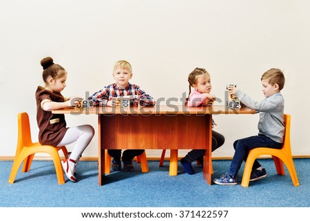 children in kindergarten playing with cubes with letters