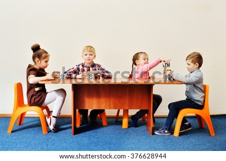 children in kindergarten playing with cubes with letters - stock photo