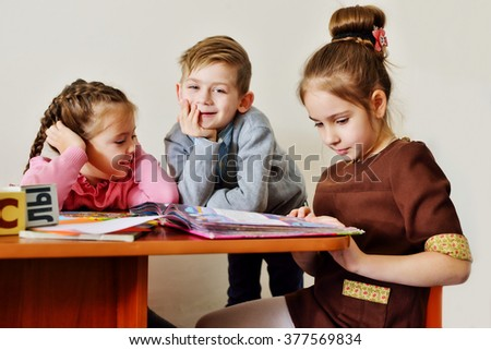 children in kindergarten reading books and laughing - stock photo