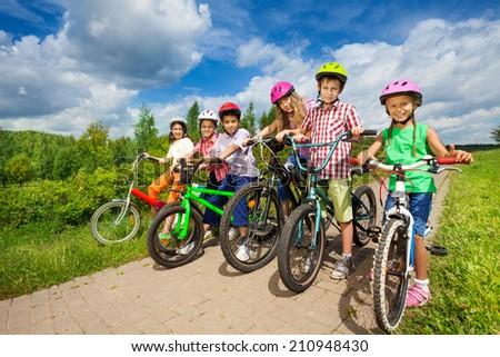 Children in row wearing helmets holding bikes - stock photo