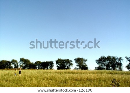 Children in rural field lined with trees - stock photo