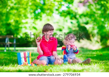 Children in school yard. Kids study. Happy laughing teenager student boy and preschool girl in the school garden reading books and having apple for healthy snack, back to school concept - stock photo