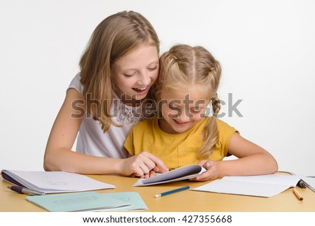Children in study group discover the world and get new knowledge. The elder sister helps the younger with homework. Girls are busy with education.