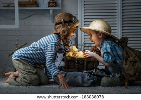 Children in the form of an aircraft pilot and traveler hunters play in his room at night - stock photo