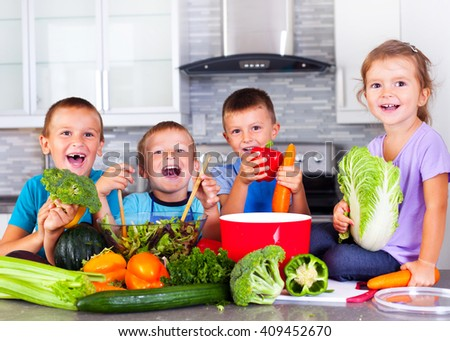 Children in the kitchen surrounded by vegetables  - stock photo