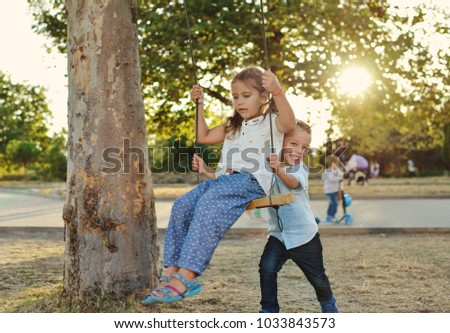 children in the park,  on and near the swing