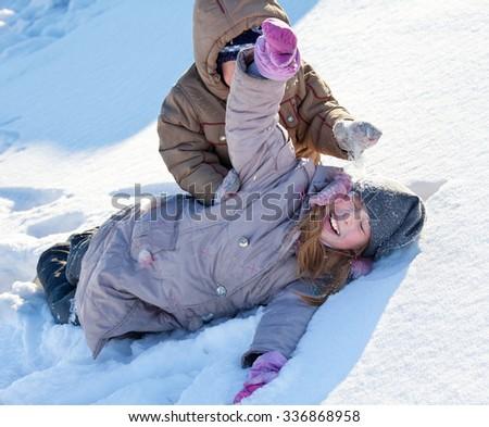 Children in the snow in winter. - stock photo