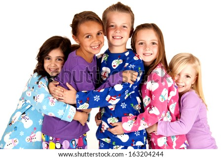 children in winter pajamas hugging each other - stock photo